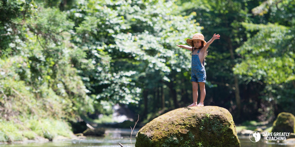 Little girl standing with arms raised on a rock in the middle of a stram